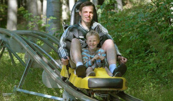 Sommerrodelbahn Vater mit Kind